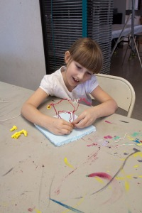 Caitlyn Conway creates a horse from electric wire during a free Family Activity Day at the Center for the Arts.